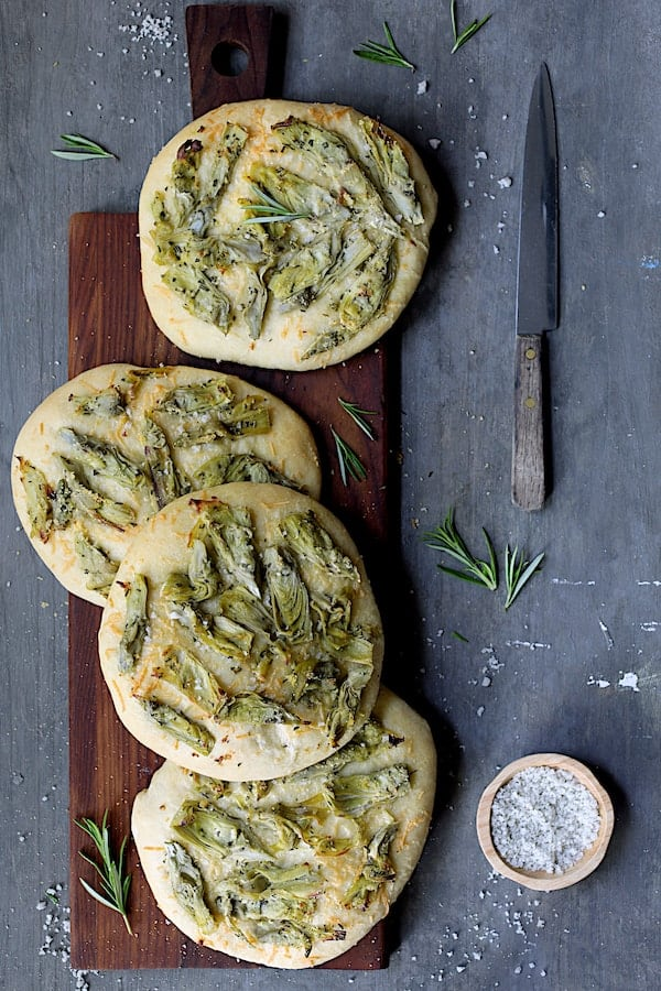 Artichoke Focaccia with Rosemary - Overhead shot on wooden breadboard with knife, fresh rosemary and coarse salt