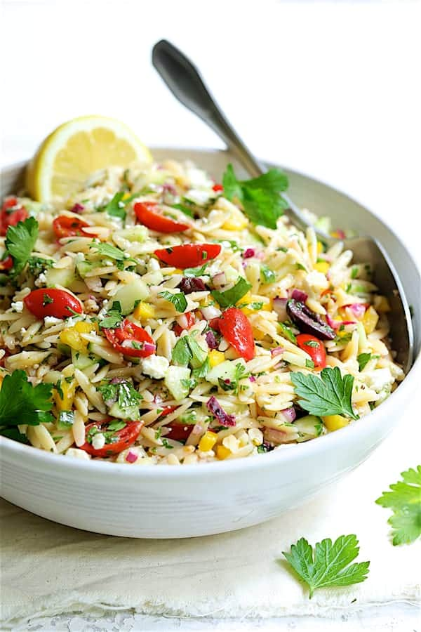 Greek Orzo Pasta Salad - Straight-on close-up shot of salad in white serving bowl with serving spoon
