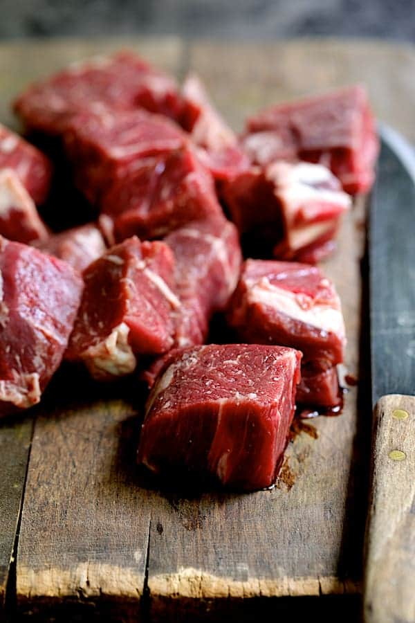 Cubed beef on wood cutting board