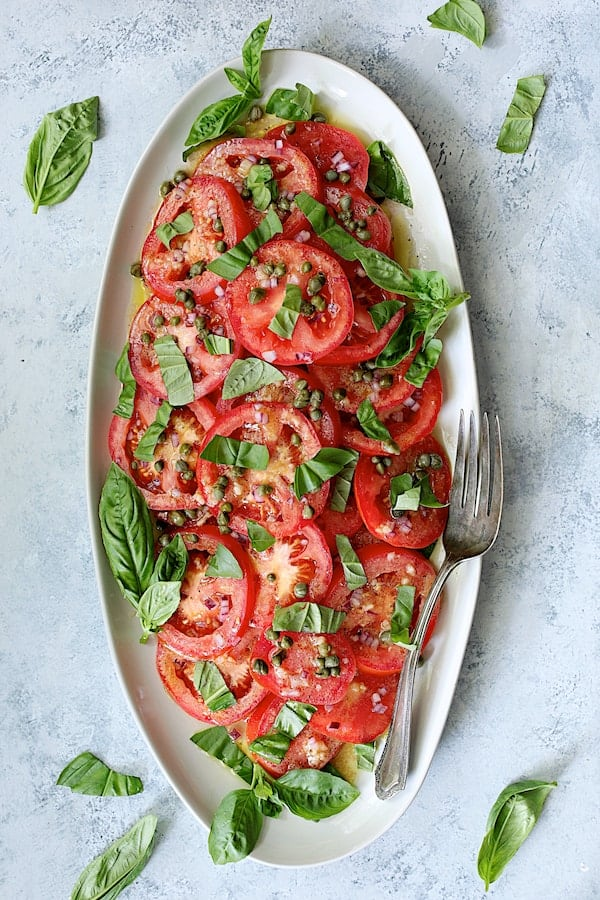 Easy Fresh Tomato Salad - Overhead shot of salad on white platter, light blue background, garnished with basil leaves