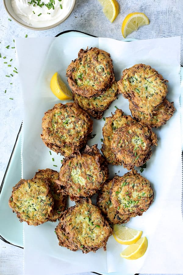 Zucchini Ricotta Fritters - Overhead hero shot of fritters on parchment paper on light blue tray with lemon wedges