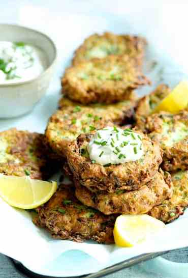 Zucchini Ricotta Fritters - Close-up shot of fritters with yogurt chive topping garnished with lemon slices
