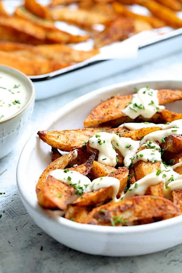 Old Bay Roasted Potato Wedges with Vermont Cheddar Cheese Sauce - Shot of potatoes in white dish drizzled with cheese sauce