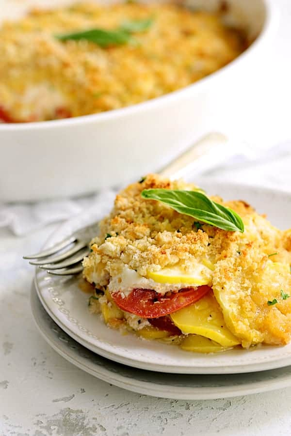 Yellow Squash and Tomato Gratin with Two Cheeses - Close-up shot of piece of the gratin on white plate