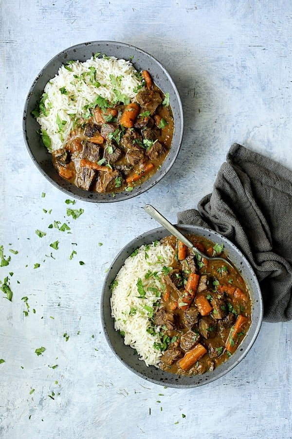 Pressure Cooker Indian Curry Beef Stew - Overhead shot in gray bowls on pale blue background garnished with cilantro