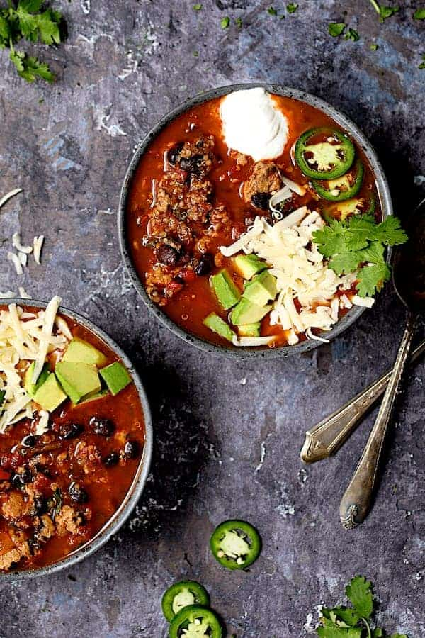 Turkey, Black Bean and Quinoa Chili - Overhead hero shot of chili on gray distressed background garnished with avocado, jalapeno, cheese and sour cream