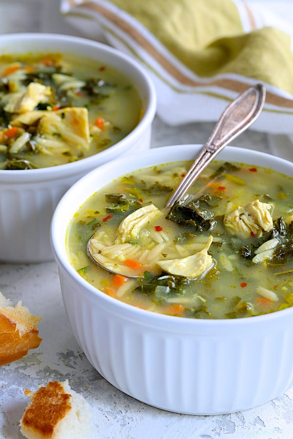 Cold-Fighting Chicken Soup with Kale and Orzo - Straight-on shot of soup in white bowls with spoon