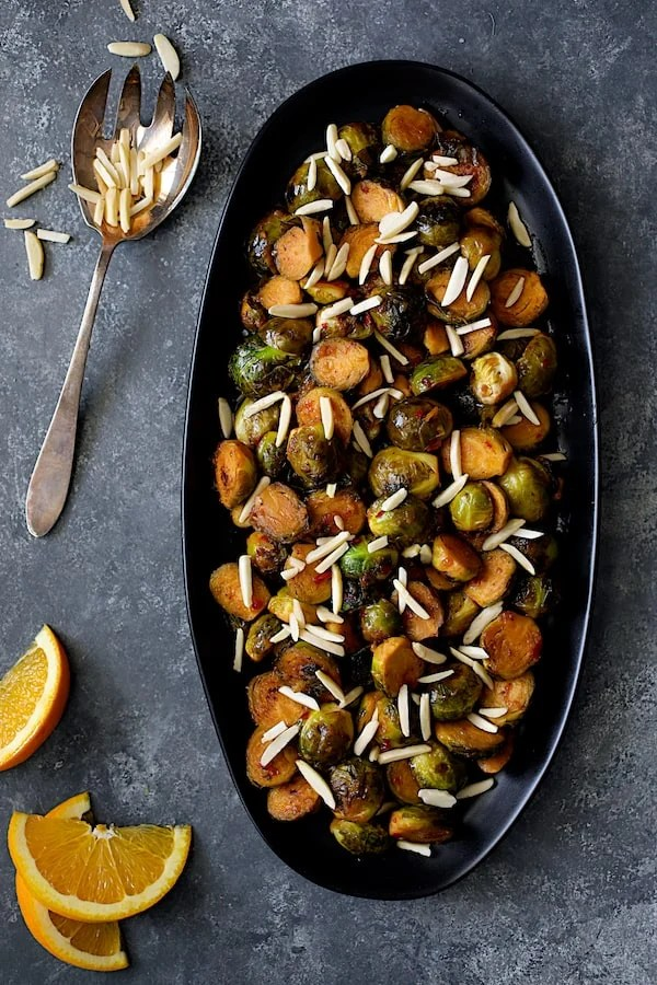 Pan-Roasted Brussels Sprouts with Thai Sweet Chili Orange Glaze - Overhead shot of sprouts on black platter with orange wedges added