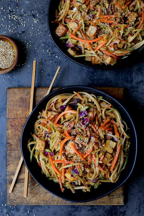 Thai Sesame Noodles with Tofu and Vegetables - Overhead hero shot of dish in black bowls on dark blue background