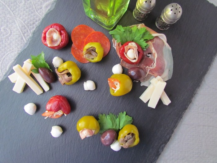 Overhead shot of anchovy and prosciutto, mozzarella stuffed cherry peppers on a black slate board with a bottle of olive oil and antique silver salt and pepper shakers.
