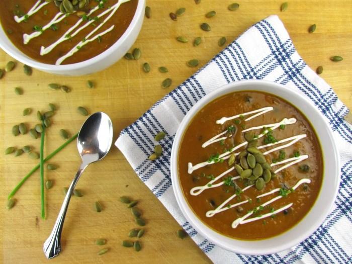 overhead shot of two bowl pumpkin black bean soup and pumpkin seeds on cutting board
