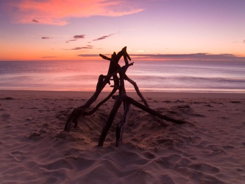 A structure made of sticks on the Hapuna beach sand during a sunset. Hawaii.