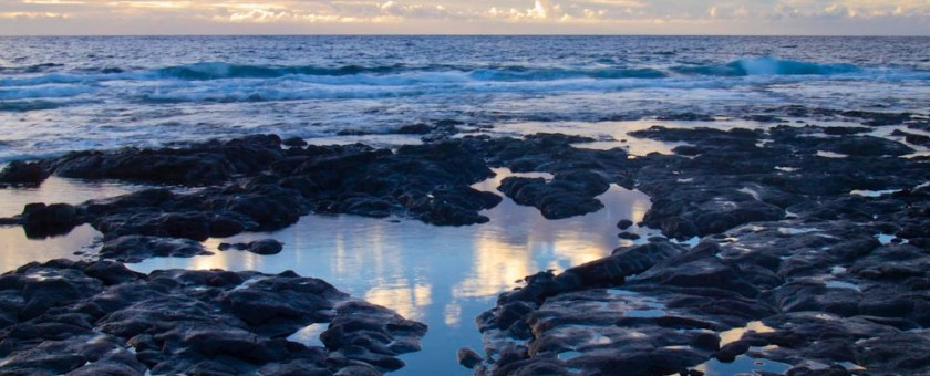 Blue Hawaiian sunset from the rocky shoreline amongst reflective pools of water