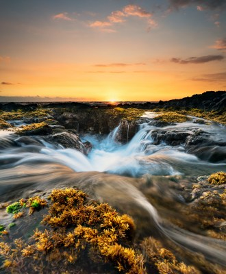 Water fills into a large hole in the Hawaiian coastline during a beautiful golden sunset.