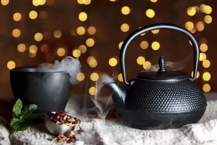 Hot steaming tea in a cup and kettle