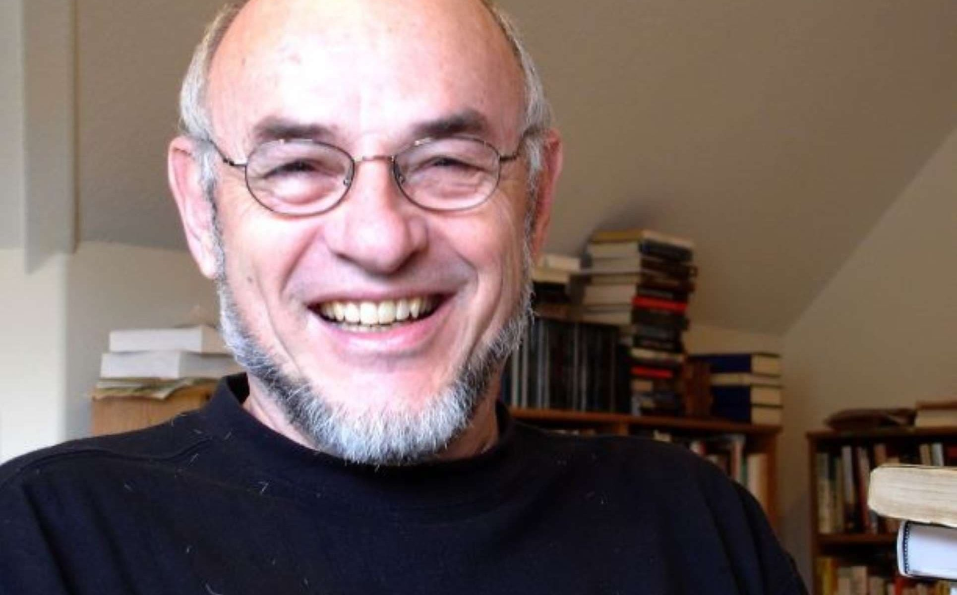 A headshot of author Richard Etulain smiling while wearing wire-rimmed glasses and a black mock neck