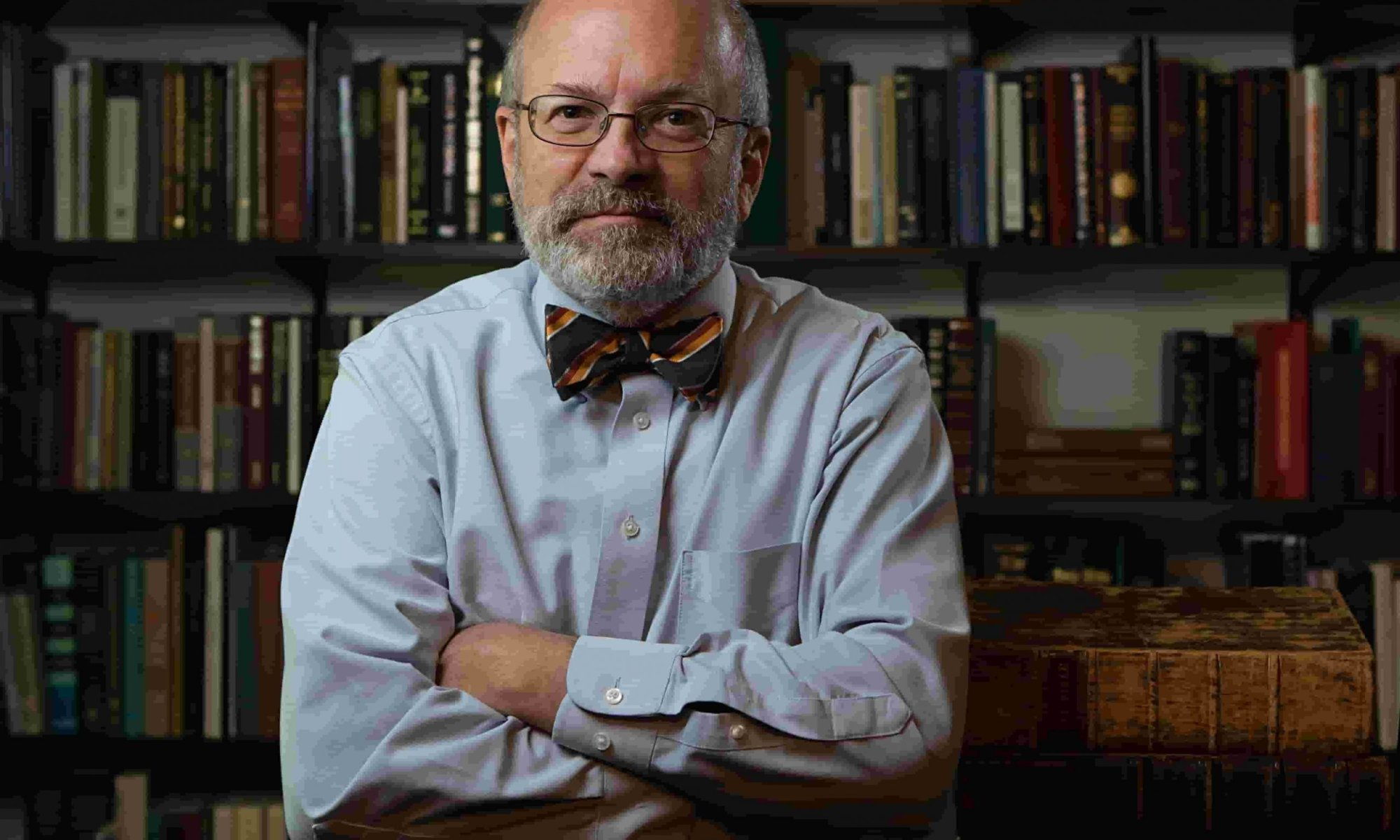 Author Kent P. Jackson sits in a library with his arms folded wearing glasses, a blue shirt, and red bowtie