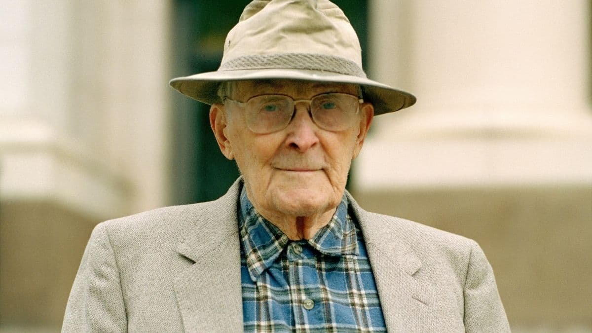 Hugh Nibley wearing a brown hat and blazer with a checkered button-up shirt