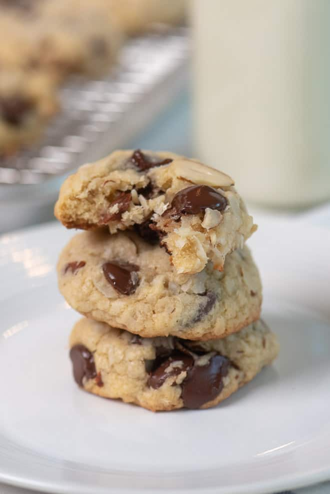 A close up image of Almond Joy Cookies stacked on a white plate. The top cookie has a bite taken out of it.