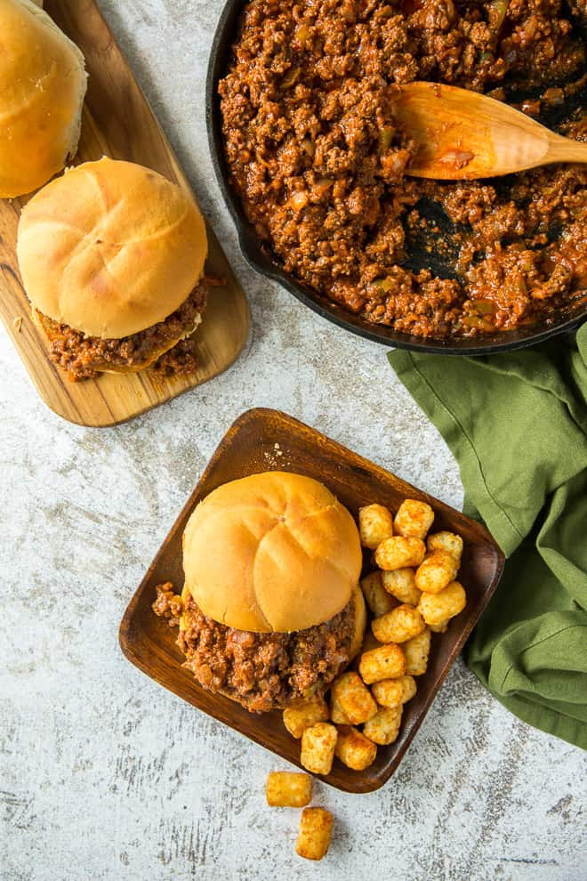 An overhead shot of a Cajun Sloppy Joe on a serving plate with tater tots with the skillet behind it.