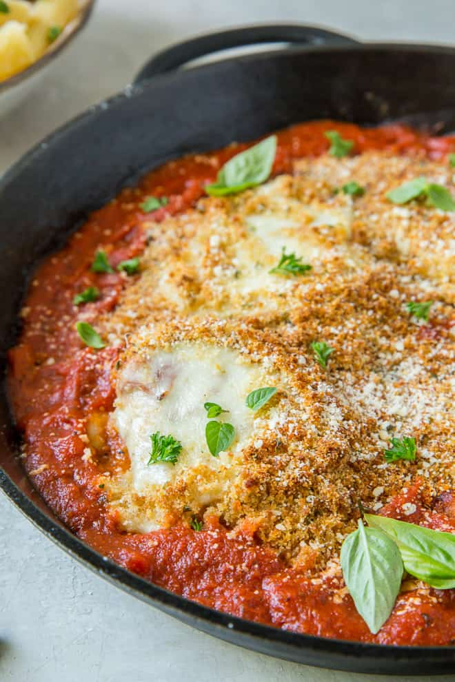 A close up image of Skillet Chicken Parmesan in a cast iron skillet.
