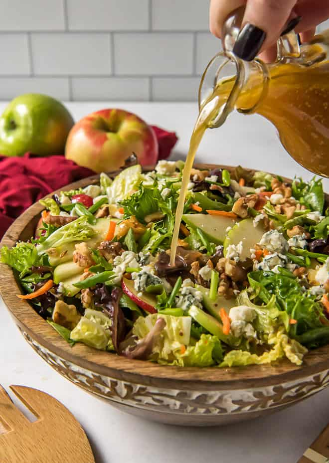 The Apple Cider Vinaigrette being poured over the top of the Apple Cabbage Salad.