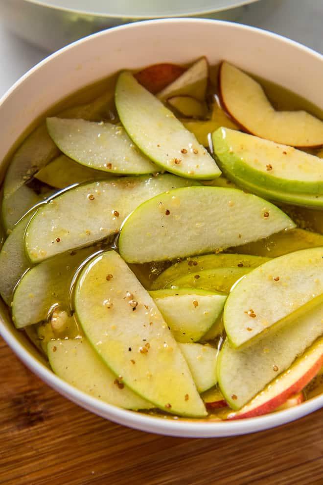 Sliced apples resting in a bowl of Apple Cider Vinaigrette.