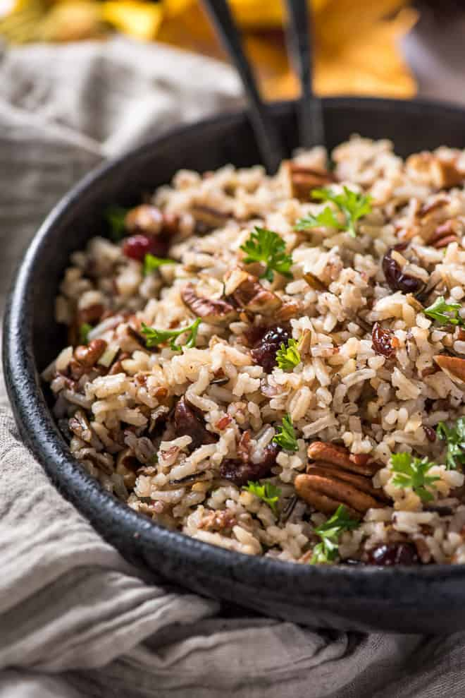 A black serving bowl filled with Wild Rice Pilaf with Cranberries and Pecans