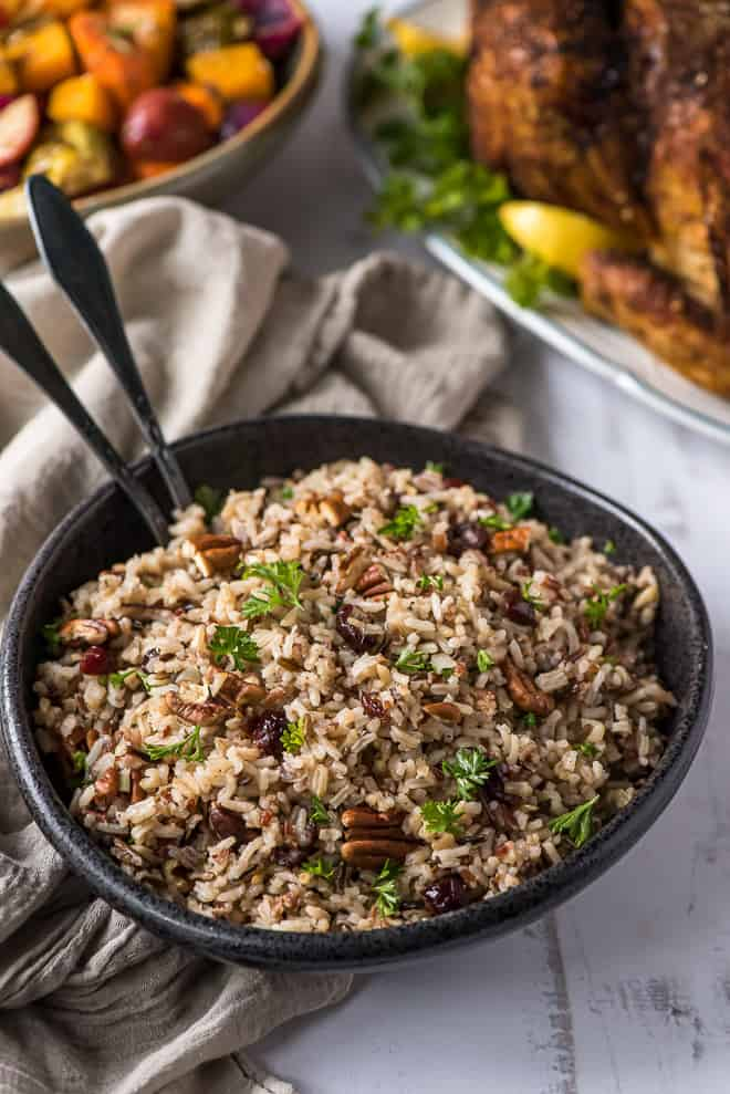 A black serving bowl filled with Wild Rice Pilaf with Cranberries and Pecans with a turkey and vegetables in the background