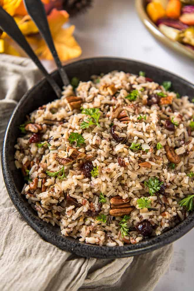 A black serving bowl filled with Wild Rice Pilaf with serving spoons