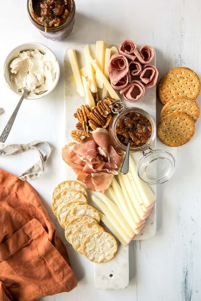 A charcuterie tray with sliced cheese, meats, crackers, cream cheese, and Bacon Jam.