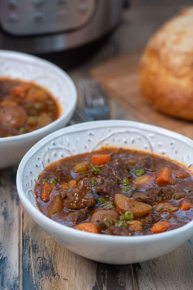 A closeup image of beef stew in a white serving bowl.