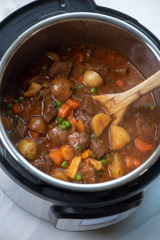 A wooden spoon stirs peas, parsley, and cornstarch slurry into the beef stew in the Instant Pot.