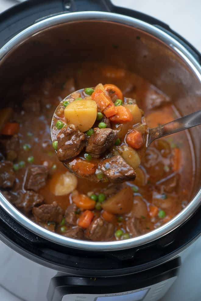 A ladle lifting Instant Pot Beef Stew out an Instant Pot.