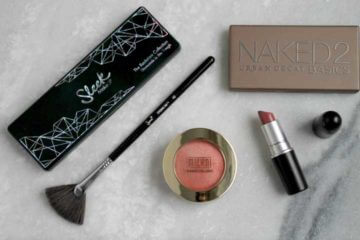 Flat lay photo of makeup with blush, lipstick, 2 eyeshadow palettes, and a fan brush