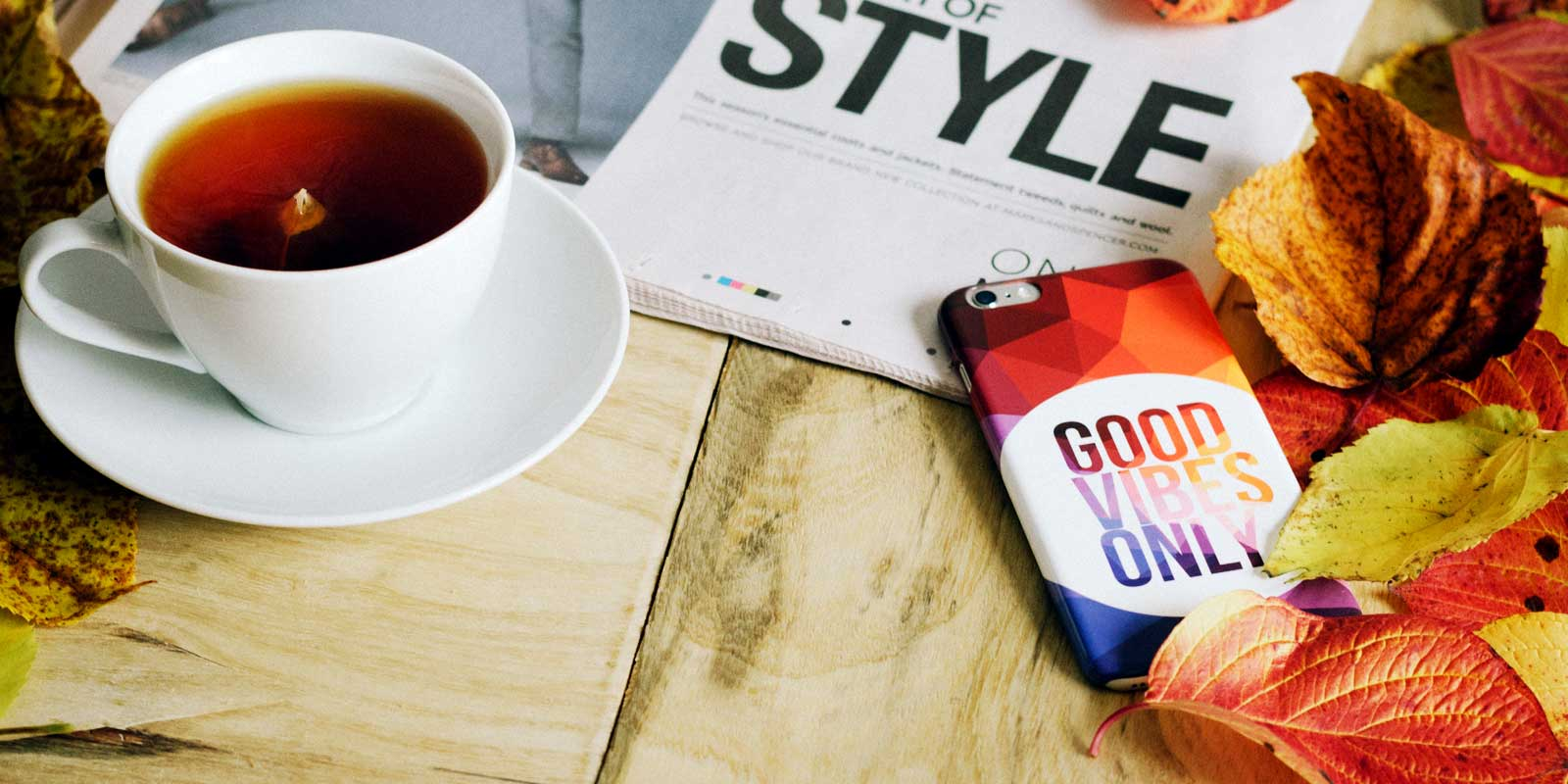 "Close up of a cup of tea, autumn leaves, a mobile phone case that says ""Good Vibes Only,"" and the corner of a magazine."