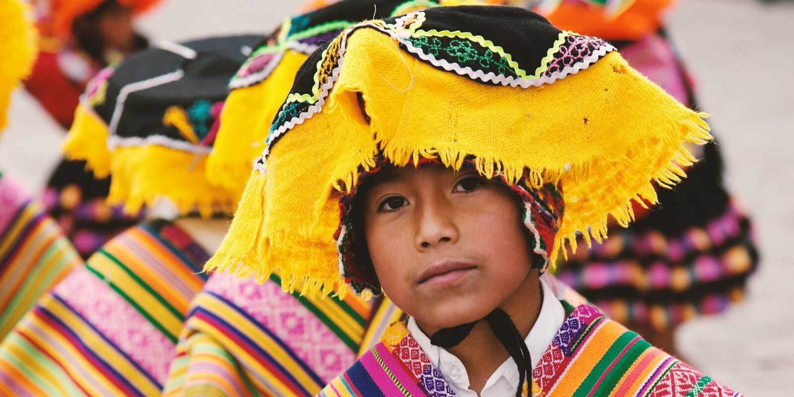 Closeup of a Peruvian child wearing colorful woven hat and clothing.