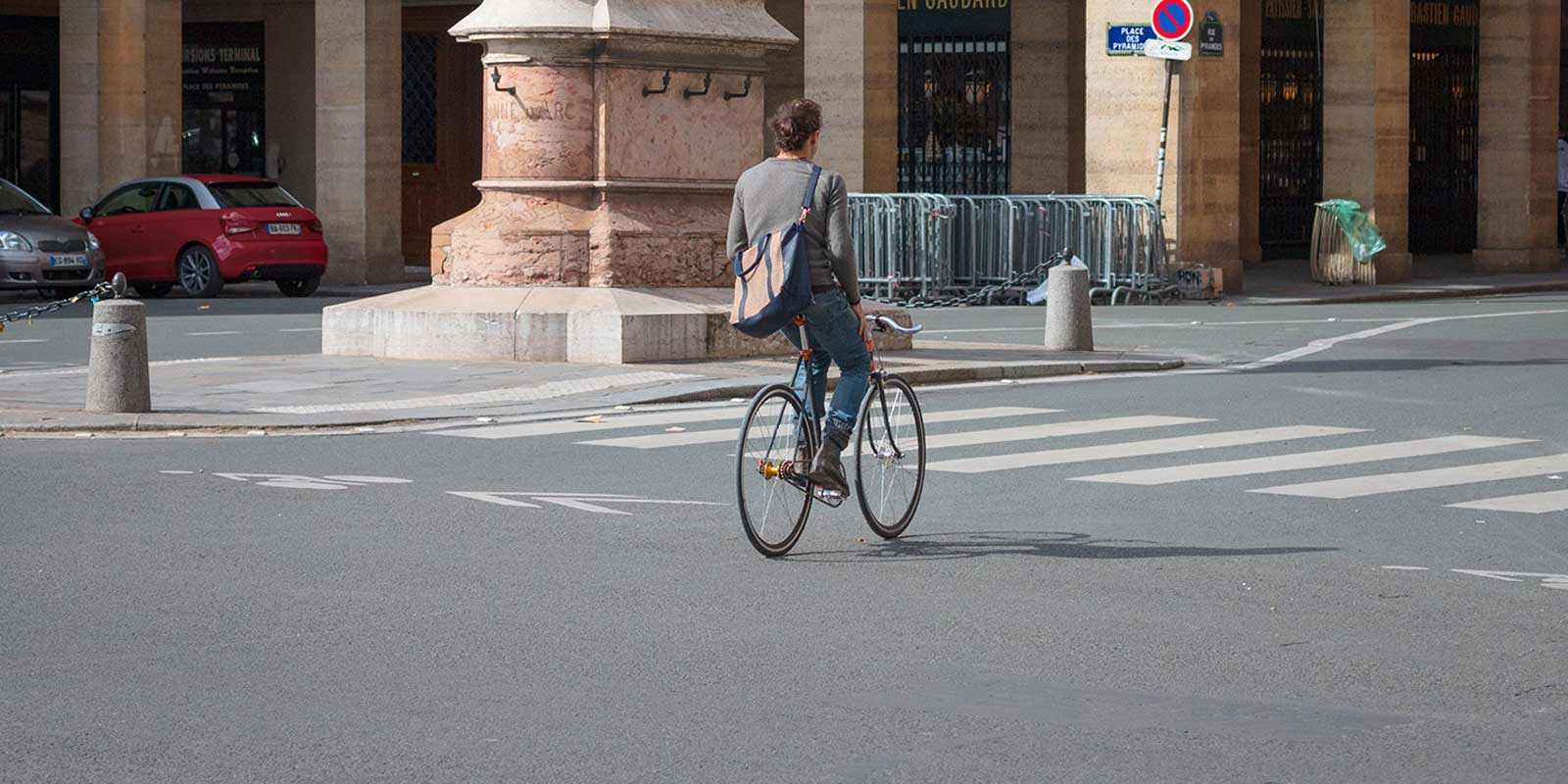 Man riding down the streets of Paris on a bicycle.