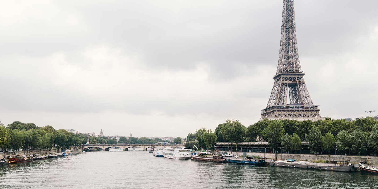 Landscape photo of the Seine River with the Eiffel Tower in the background on a gray, stormy day.
