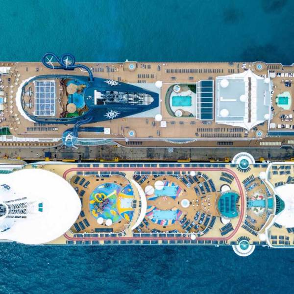 Aerial view of 2 cruise ships docked side by side.
