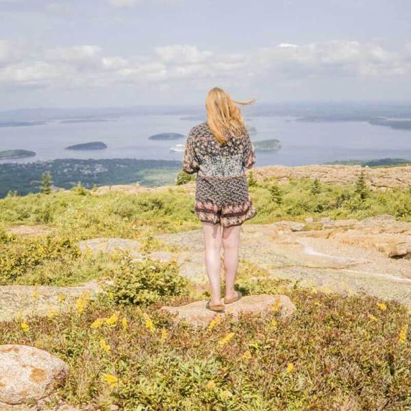 Travel blogger Meg Frost on top of Cadillac Mountain, overlooking downtown Bar Harbor, Maine and the Porcupine Islands.