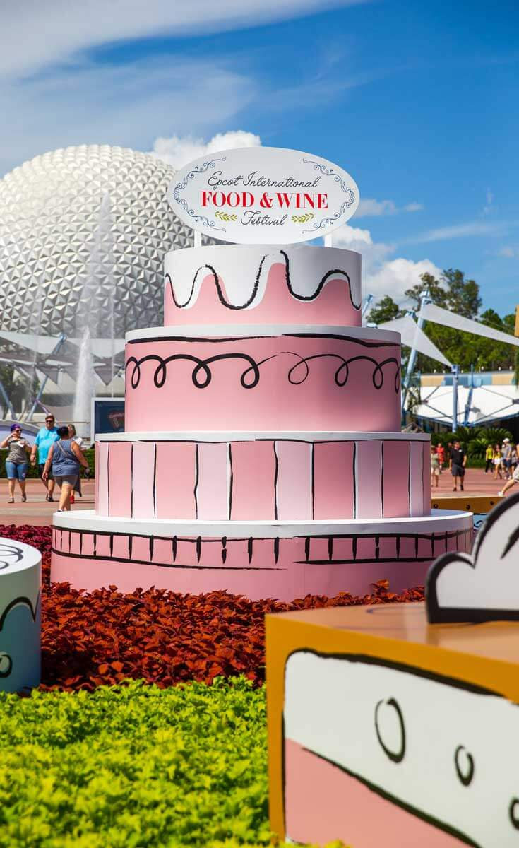 Closeup of an Epcot International Food & Wine Festival artwork at the Epcot entrance. Fully shown is a 4 tier giant (fake) pink cake with a festival sign on top.
