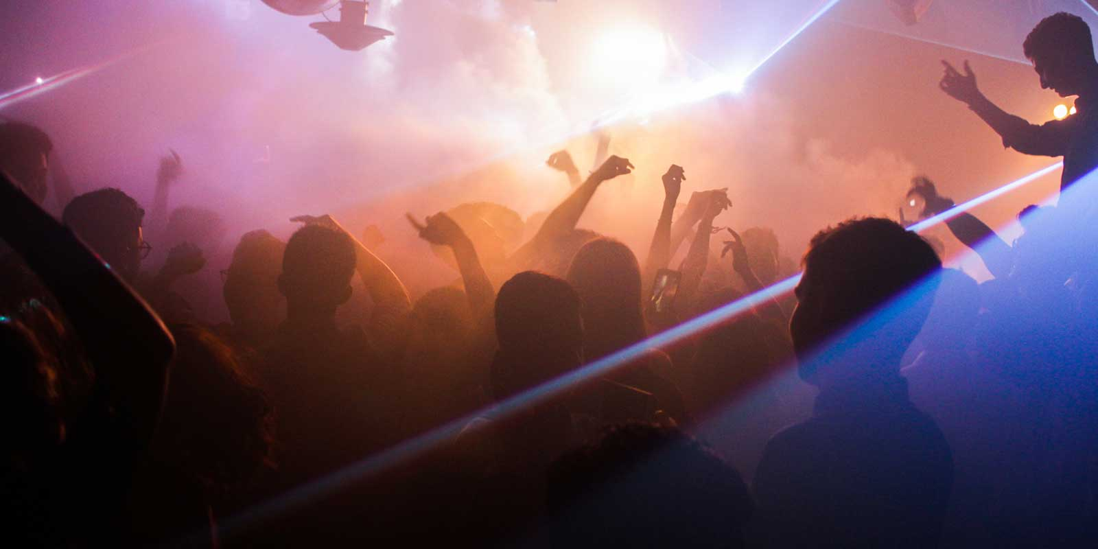 Photo inside a nightclub with silhouettes of dancing people and flashing lights.