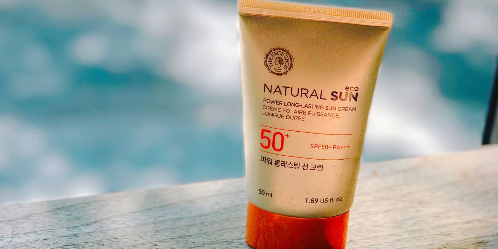 Closeup of a tube of sunscreen sitting next to a pool.