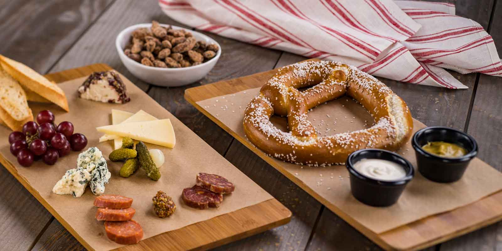 Flat lay photo of the food available at the BaseLine Tap House at Disney World's Hollywood Studios. In the photo are a giant baked pretzel and dips, a charcuterie board, and bar nuts.