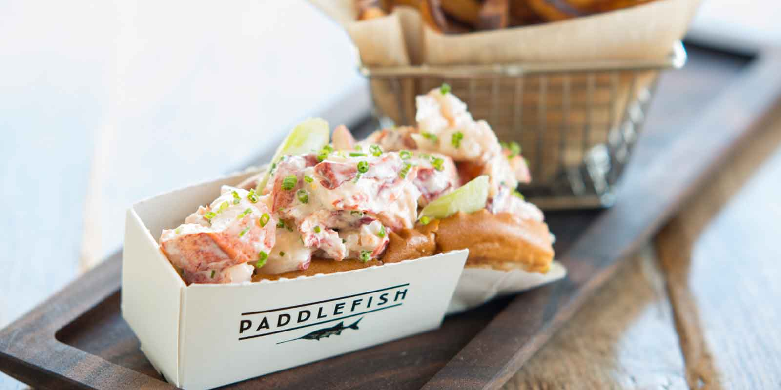 Close up of a lobster roll and bucket of french fries from Paddlefish.
