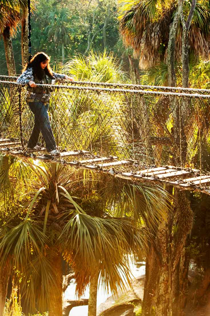 A woman walks across a rope and plank bridge at Disney's Animal Kingdom park.