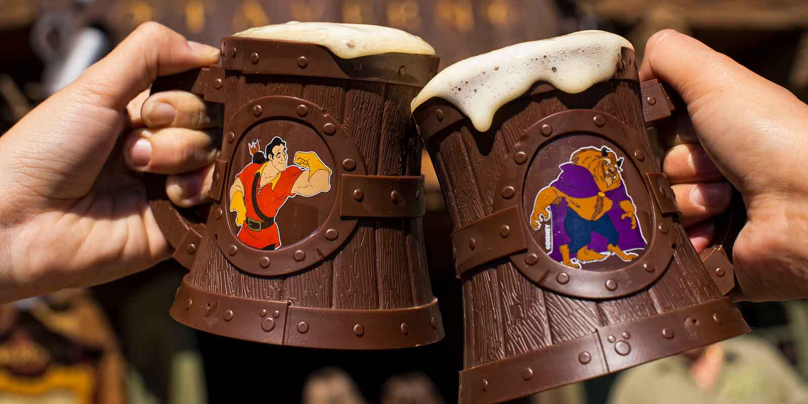 Two adults clink plastic mugs overflowing with Le Fou's Brew at Magic Kingdom.