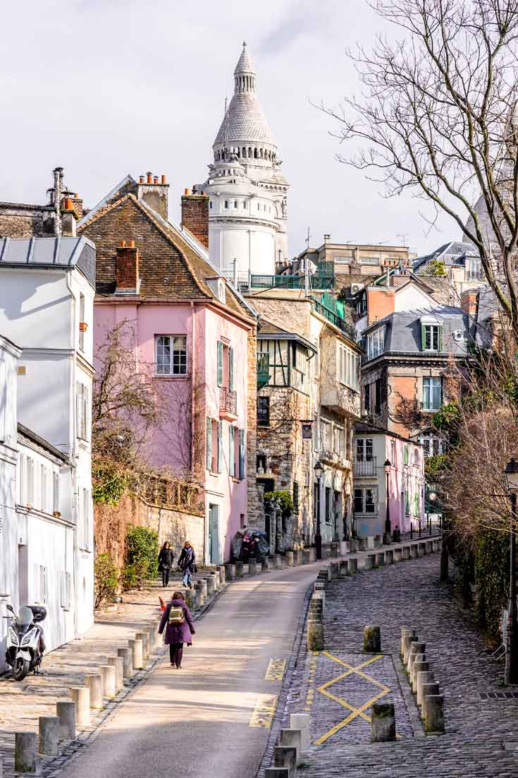 Portrait shot of a hilly street in Montmartre, Paris, France with colorful buildings, such as white, pink, and yellow.