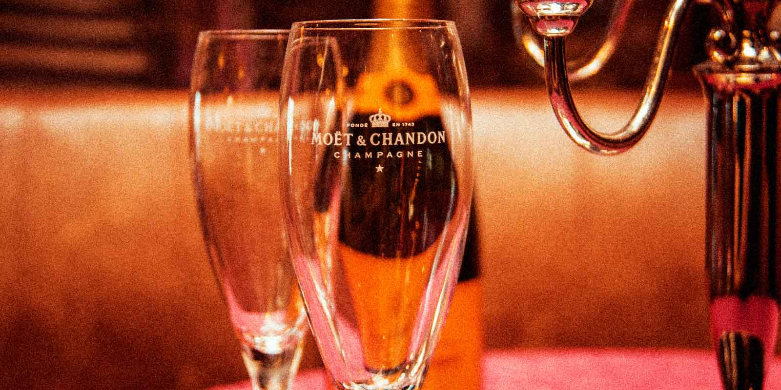 Closeup of 2 champagne glasses with the Moët & Chandon label.